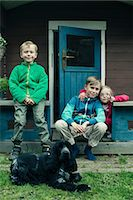 Portrait of siblings with dog sitting on porch Stock Photo - Premium Royalty-Freenull, Code: 698-07635679