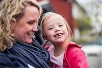Portrait of happy girl with down syndrome carried by mother Stock Photo - Premium Royalty-Freenull, Code: 698-07635702