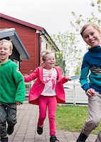 Girl with brothers running in lawn Stock Photo - Premium Royalty-Freenull, Code: 698-07635704