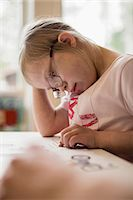 Girl with down syndrome studying at table Stock Photo - Premium Royalty-Freenull, Code: 698-07635710