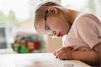 Girl with down syndrome studying at table Stock Photo - Premium Royalty-Freenull, Code: 698-07635711