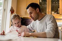 Father assisting handicapped daughter in studying at home Stock Photo - Premium Royalty-Freenull, Code: 698-07635713