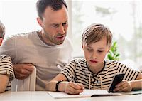 Boy using mobile phone while writing at table by father in house Stock Photo - Premium Royalty-Freenull, Code: 698-07635723