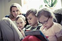 Siblings sitting with mother in house Stock Photo - Premium Royalty-Freenull, Code: 698-07635732