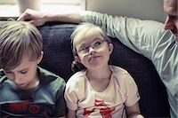 Girl with down syndrome looking at father by brother on sofa Stock Photo - Premium Royalty-Freenull, Code: 698-07635733