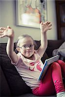 Portrait of handicapped girl with digital tablet raising arms on sofa Stock Photo - Premium Royalty-Freenull, Code: 698-07635734