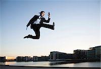 fit people - Mid adult businessman jumping mid air, Copenhagen harbor, Denmark Stock Photo - Premium Royalty-Freenull, Code: 649-07647987