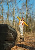 Young woman balancing on log on forest assault course Stock Photo - Premium Royalty-Freenull, Code: 649-07648078