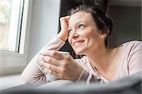 Mid adult woman looking out of window with coffee Stock Photo - Premium Royalty-Freenull, Code: 649-07648291