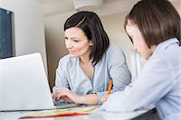Mother using laptop, daughter writing Stock Photo - Premium Royalty-Freenull, Code: 649-07648309