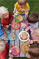 Overhead view of seven children eating spaghetti at picnic table Stock Photo - Premium Royalty-Freenull, Code: 649-07648415