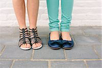 Close up of two sisters legs and footwear Stock Photo - Premium Royalty-Freenull, Code: 649-07648446
