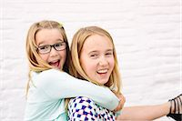 Two sisters playing piggyback Stock Photo - Premium Royalty-Freenull, Code: 649-07648447