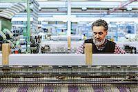 Male factory worker on weaving machine in woollen mill Stock Pho