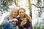 Mother and teenage daughter looking at smartphone