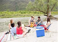 Friends sitting by river, playing guitar Stock Photo - Premium Royalty-Freenull, Code: 649-07648547