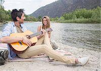 Friends sitting beside river, playin