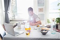 Young man having breakfast and using laptop Stock Photo - Premium Royalty-Freenull, Code: 649-07648561