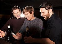 Three male friends looking at smartphone in nightclub Stock Photo - Premium Royalty