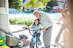 Grandfather and granddaughter on bike in garage