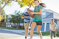 Family playing football in sunny street Stock Photo - Premium Royalty-Freenull, Code: 6113-07648790