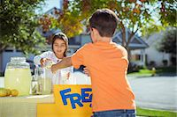 person holding sign - Boy buying lemonade at lemonade stand Stock Photo - Premiu