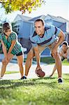 Family playing football in grass