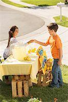 Boy buying lemonade at lemonade stand Stock Photo - Premium Royalty-Freenull, Code: 6113-07648870