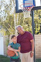 Portrait of grandfather and granddaughter playing basketball Stock Photo - Premium Royalty-Freenull, Code: 6113-07648881