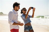 south american woman - Couple sharing music from smartphone, Arpoador beach, Rio De Janeiro, Brazil Stock Photo - Premium Royalty-Free, Artist: Ikon Images, Code: 614-07652221