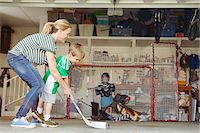 sports and hockey - Mother playing hockey in garage with two sons Stock Photo - Premium Royalty-Freenull, Code: 614-07652251