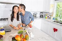 Romantic mid adult couple preparing sandwich at kitchen counter Stock Photo - Premium Royalty-Freenull, Code: 614-07652357
