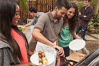 Friends sitting around table sharing barbecue food Stock Photo - Premium Royalty-Freenull, Code: 614-07652465