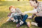 Mid adult mother, daughter and baby son on grass in park