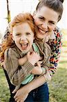 Portrait of mid adult mother hugging daughter in park
