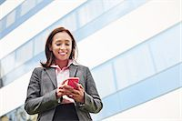 Young female businesswoman texting on smartphone outside office Stock Photo - Premium Royalty-Freenull, Code: 614-07652567