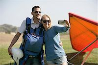 Couple taking selfie, hang glider in background Stock Photo - Premium Royalty-Freenull, Code: 614-07652575