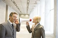 Businesswoman shouting to colleague through bullhorn in lobby Stock Photo - Premium Royalty-Freenull, Code: 618-07653709