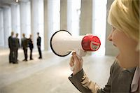 Businesswoman shouting to colleagues through bullhorn in lobby Stock Photo - Premium Royalty-Freenull, Code: 618-07653710