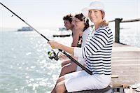 Friends fishing off pier at ocean Stock Photo - Premium Royalty-Freenull, Code: 635-07670939