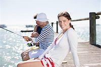 Friends fishing off pier at ocean Stock Photo - Premium Royalty-Freenull, Code: 635-07670940