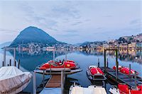Moored pedal boats by the promenade in front of Monte San Salvatore and city lights at Lago Lugano at dawn in spring, Lugano, Switzerland Stock Photo - Premium Rights-Managednull, Code: 700-07672086