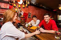 Female bartender serving beer to men at bar counter Stock Photo - Premium Royalty-Freenull, Code: 693-07672598