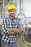 Portrait of worker with arms crossed leaning on large valve in industry Stock Photo - Premium Royalty-Freenull, Code: 693-07672631