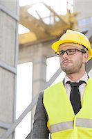 professional (pertains to traditional blue collar careers) - Young male engineer wearing hard hat looking away at construction site Stock Photo - Premium Royalty-Freenull, Code: 693-07672633