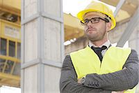 professional (pertains to traditional blue collar careers) - Young male architect standing arms crossed at construction site Stock P