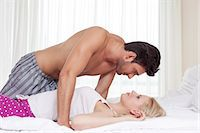 Side view of passionate young couple in bed Stock Photo - Premium Royalty-Freenull, Code: 693-07672701