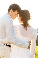 Rear view of romantic couple standing arms around against clear sky Stock Photo - Premium Royalty-Freenull, Code: 693-07672758