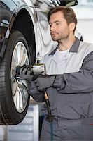 Repairman adjusting car's wheel in workshop Stock Photo - Premium Royalty-Freenull, Code: 693-07672919