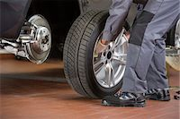 Low section of repairman fixing car's tire in repair shop Stock Photo - Premium Royalty-Freenull, Code: 693-07672923